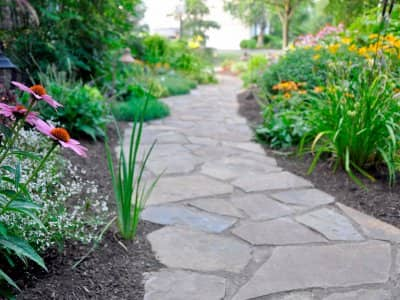 Landscaped grounds with a stone-paved path, mulch and flowers