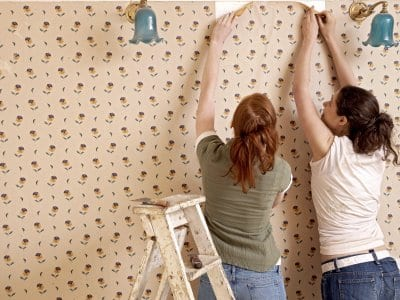 two women removing wallpaper