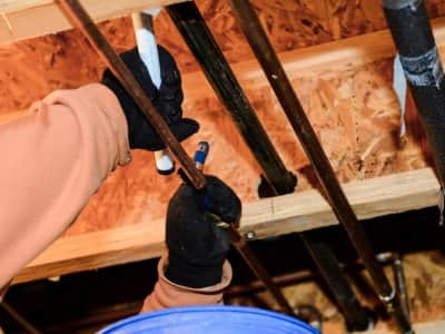 gloved hands installing copper pipes