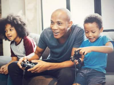 Father and kids playing video games