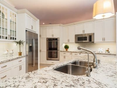 Kitchen sink with appliances and cabinets in background