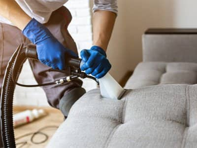 Man professionally cleaning couch upholstery