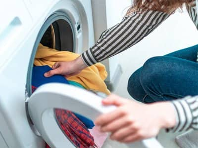 Woman putting clothes in the dryer