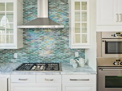 Kitchen with silver blue tiles and white cabinets
