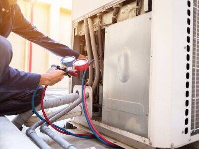 Technician is checking air conditioner and measuring equipment for filling air conditioners