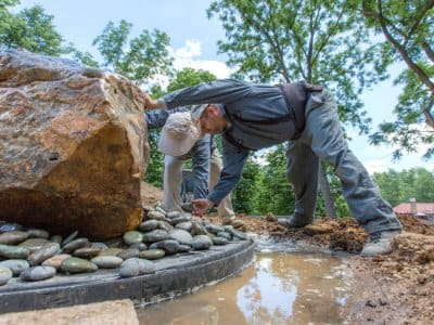 Landscapers placing smooth gray decorative stones around the base of a 1-ton bubbling boulder fountain