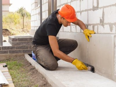 construction worker waterproofing the foundation of a house