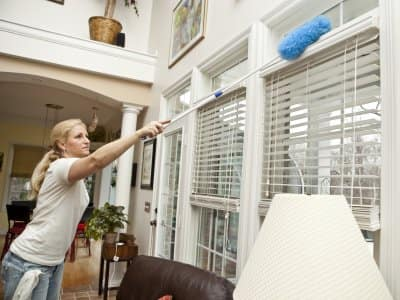 woman dusting blinds