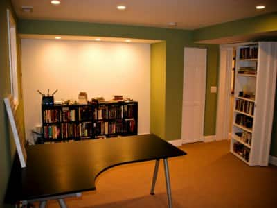 remodeled basement with built-in bookshelf that doubles as secret door to office