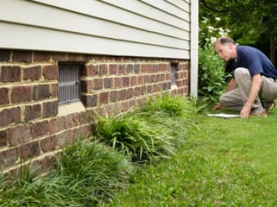 Foundation inspector looking at a brick foundation with vents