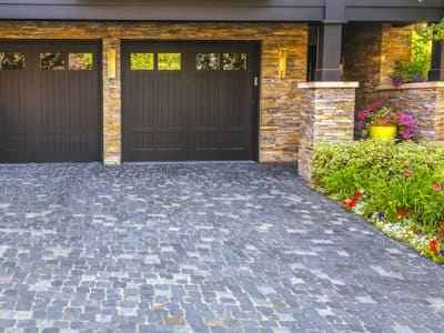 brown double garage doors and stone paved driveway