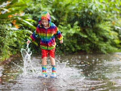 Child playing in a large puddle in the rain