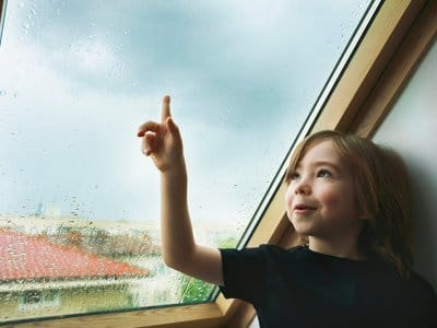 Child watching the rain from a rooftop window