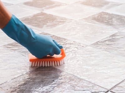 Gloved hand with scrub brush cleaning tile