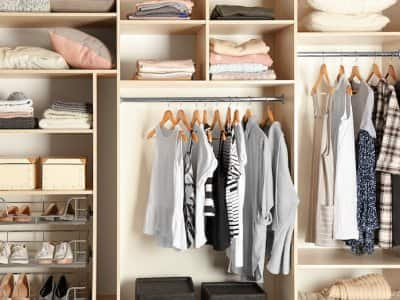 a beige closet minimally filled with clothing and shoes