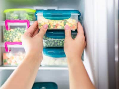 Woman taking frozen food out of freezer