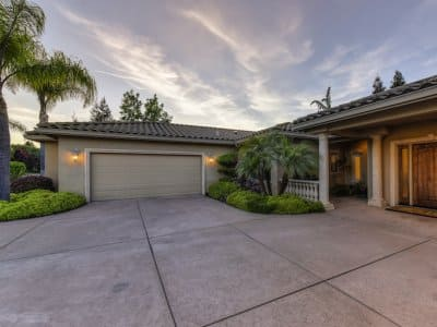 a concrete driveway outside a garage and home during sunset