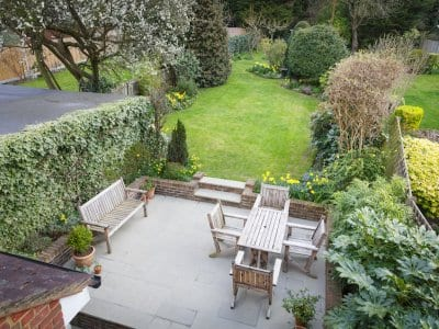 overhead view of concrete patio with lawn furniture next to lush garden flowers and plants and grassy yard