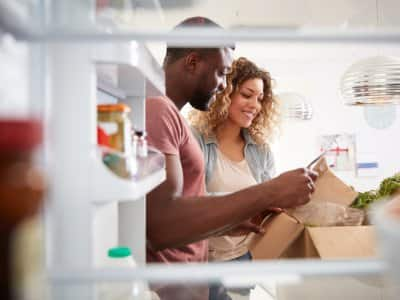 View looking out from inside of refrigerator as couple unpack groceries