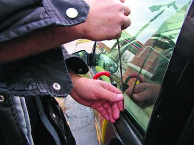 man holding unlocking tool at vehicle window