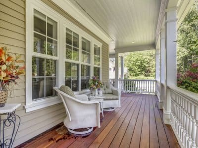 a deck features patio furniture, wood floor, and four large windows