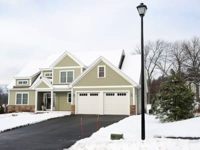 a home with snow on the grass and a clear driveway