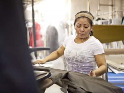 woman positions suit pants on dry cleaning pressing machine