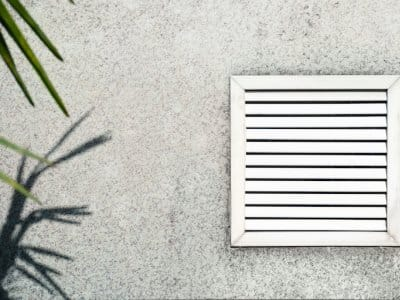 vent with white shutters on the background of gray concrete under the leaves of the palm