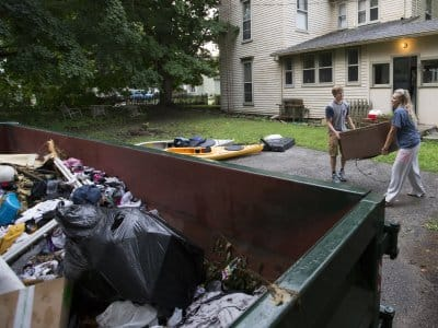 people hauling junk out to a dumpster