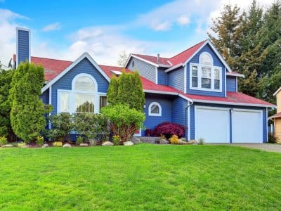 view of bright blue suburban home with green yard and landscaping