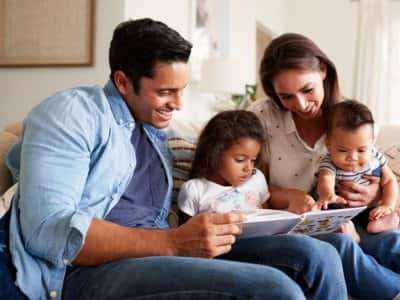 Young Hispanic family sitting on couch in living room
