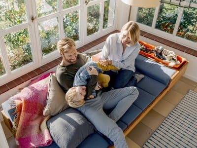 family playing on couch in sunroom
