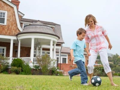Family playing with a ball with a house in the background