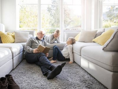 elderly man and two young kids read book in front of large windows between two white couches