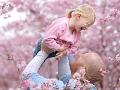Father holding smiling daughter among cherry blossom trees