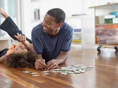 A father and daughter put together a puzzle