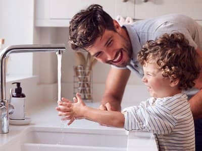 Father helps son wash his hands