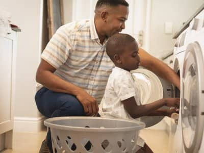 A father and his son put clothes in the dryer