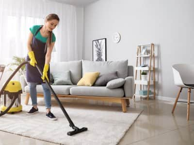 A female janitor vacuums a living room