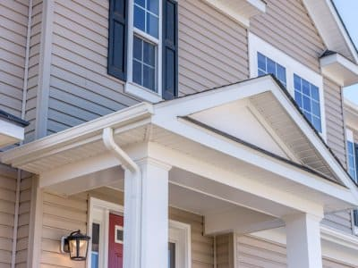 Portico leading to the entrance of vinyl horizontal lap siding covered building, with a roof structure over a walkway, supported by white rectangular columns on a single family home