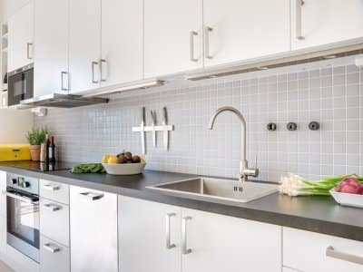 interior view of kitchen with gray countertop and white flat cabinet doors with silver handles