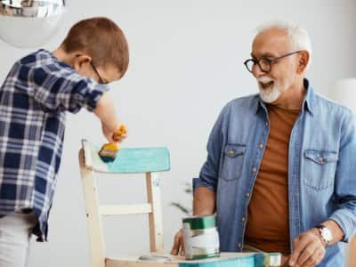 Grandfather and grandson painting a chair blue