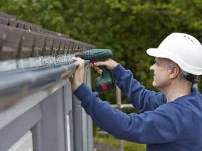 Workman replace guttering on a house