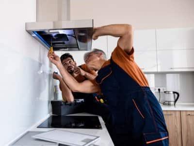 Handyman working under vent with homeowner