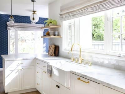 a home kitchen with white cabinets, marble countertop, gold fixtures, blue walls, and light streaming through the window