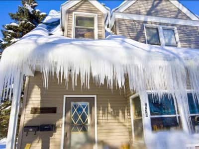 large icicles hanging on roof of beige house