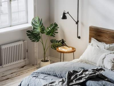 The interior of a bedroom with a potted plant, a night table and a heater