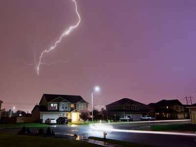 A lightning during a storm strikes above a house