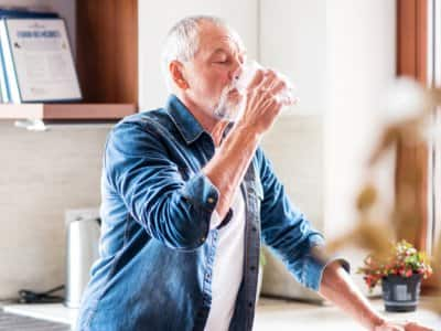 Senior man cooling off with drink of water
