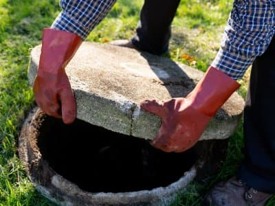man with red gloves opens lid of septic tank in grassy yard